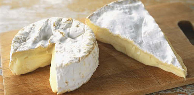 camembert and brie wedge side by side on cheese board