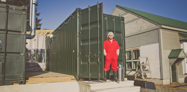 Brian Civitello stands outsides of one of his cheesemaking pods for Mystic Cheese