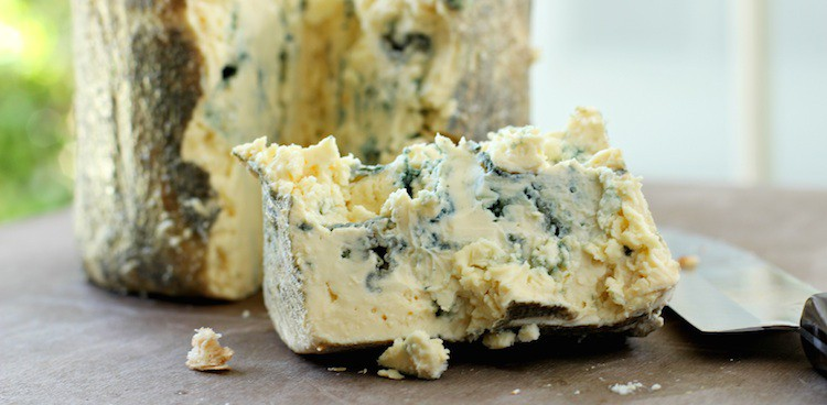 Creamy, leaf-wrapped blue cheese broken apart with a knife