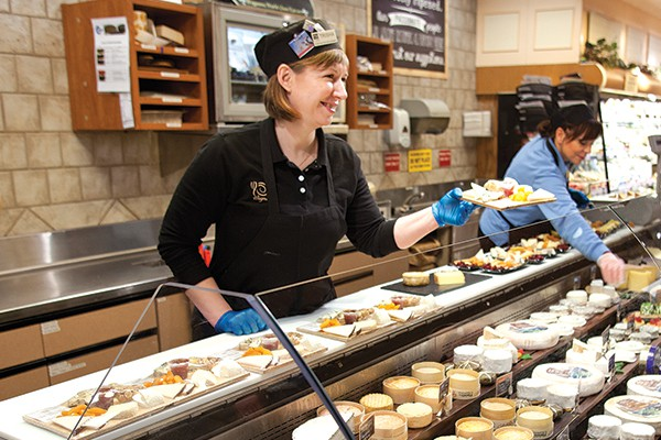 Trisha Szklany offers cheese to customers at a Wegmans in Pittsford, N.Y.